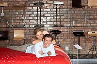 Couple shopping in furniture store, lying on new bed, smiling, portrait