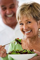 Senior woman eating fresh salad, man looking on, smiling, close-up, portrait, focus on foreground