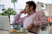 Businessman sitting at balcony table with laptop, coffee and croissants, hand on chin, thinking