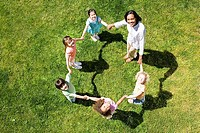 Teacher playing game of ring-a-ring-o´roses with children 3-5 on grass, portrait, overhead view