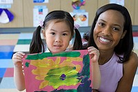Girl 3-5 sitting beside teacher in classroom, holding painting, smiling, front view, portrait