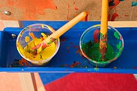 Multi-coloured paint pots in tray in nursery school classroom, close-up, overhead view still life