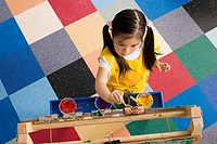 Girl 3-5 painting picture on easel in classroom, overhead view
