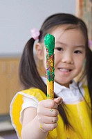 Girl 3-5 holding up paintbrush, smiling, front view, close-up, portrait differential focus
