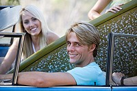 Teenage couple 17-19 sitting in car with surfboard, smiling, side view, portrait