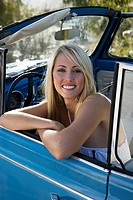 Blonde teenage girl 17-19 sitting in blue convertible car, smiling, portrait
