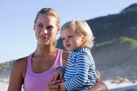 Mother carrying daughter 2-3, standing on beach, smiling