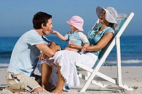 Family relaxing on beach, girl 2-3 sitting in mother´s lap, feeding father, laughing, side view