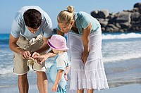 Father showing daughter 2-3 crab on beach, mother looking on