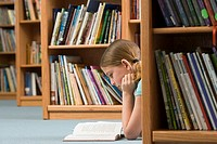 Girl 10-12 lying on floor beside bookshelf in library, reading book, profile