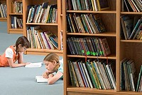 Two girls 10-12 lying on floor beside bookshelf in library, reading books, side view