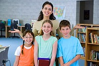 Female teacher standing with three pupils 10-12 in classroom, smiling, front view, portrait