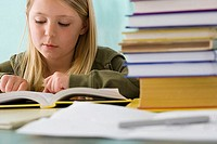 Girl 9-11 reading textbook at desk in classroom, surface level differential focus