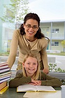 Girl 9-11 reading book at desk in classroom, female teacher assisting, smiling, portrait