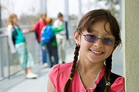 Girl 10-12 in spectacles leaning against wall, smiling, portrait, friends in background