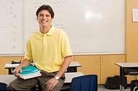 Male school teacher sitting with textbook on desk in classroom, smiling, portrait