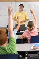 Male teacher standing beside whiteboard in classroom, children 9-11 with hands raised