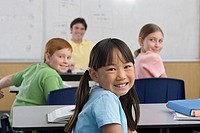 Teacher sitting beside whiteboard in classroom, focus on children 9-11 at desks, smiling, portrait
