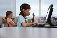 Two girls 9-11 using computer at desk in classroom, profile, surface level