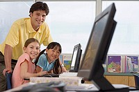 Two girls 9-11 using computer at desk in classroom, male teacher assisting, smiling, portrait