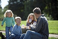 Two generation family having tea and sandwiches in park
