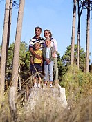 Two generation family standing on top of tree stump in wood, smiling