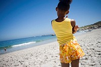 Girl 9-11 in yellow vest and shorts standing on beach, looking at sea, rear view tilt