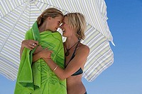 Mother embracing daughter 9-11 wrapped in green beach towel beneath sunshade, rubbing noses