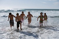 Group of teenagers 13-15 playing in surf at beach, front view