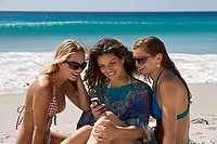 Three young women sitting on beach, text messaging on mobile phone, smiling