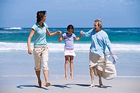 Mother and grandmother swinging girl 7-9 on beach, smiling, front view