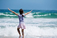 Girl 7-9 standing in surf at beach, arms outstretched, rear view
