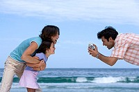 Two generation family standing on beach, man filming with camcorder, smiling, profile