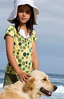 Girl 6-8 in sun hat standing on beach with dog, smiling, side view, portrait