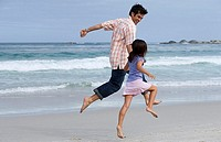 Father and daughter 6-8 skipping on beach near water's edge, side view