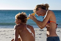 Teenage girl 17-19 squirting sun cream on boyfriend's back at beach, laughing, rear view