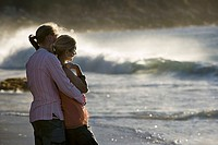Affectionate teenage couple 17-19 standing on beach near surf, boy embracing girl, side view