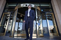 Businessman in sunglasses standing in front of revolving door, low angle view