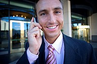 Businessman standing outside building, using mobile phone, smiling, front view, portrait