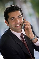 Businessman using mobile phone, smiling, close-up, portrait