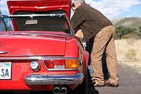 Two men looking at engine of red convertible car at roadside (thumbnail)