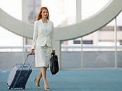 Businesswoman walking in airport with luggage and briefcase