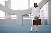 Businesswoman in white suit carrying briefcase, smiling, front view, portrait