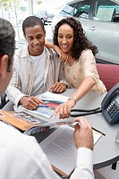 Salesman and young couple sitting at desk in car showroom, woman pointing at brochure, smiling