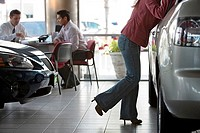 Salesman and male customer sitting at desk in car showroom, woman looking closely at silver saloon