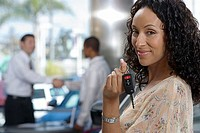 Salesman and customer shaking hands in car showroom, focus on woman holding key, smiling, portrait