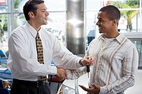 Salesman handing male customer key in car showroom, shaking hands, smiling, side view