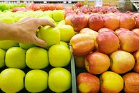 Woman reaching for green apple on display in supermarket, close-up, rear view