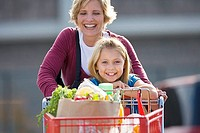 Mother and daughter 7-9 pushing shopping trolley in supermarket car park, front view, smiling, portrait