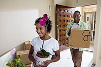 Couple moving house, woman carrying plant pot, man carrying cardboard box in hallway, smiling